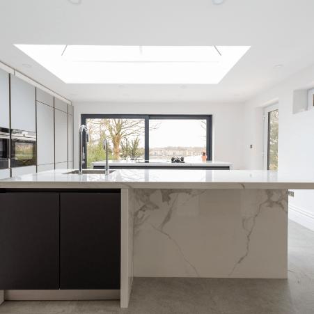 A modern kitchen with white marble worktops